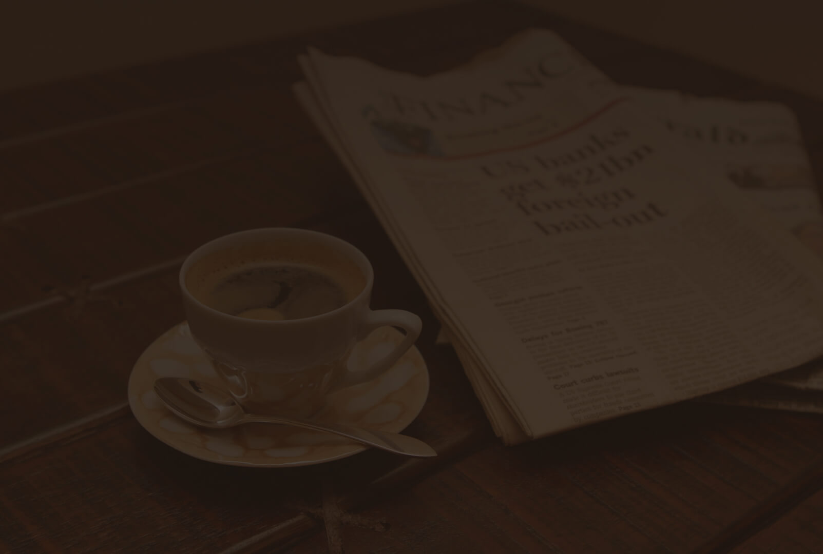 filiżanka z kawą na drewnianym stole obok gazety
