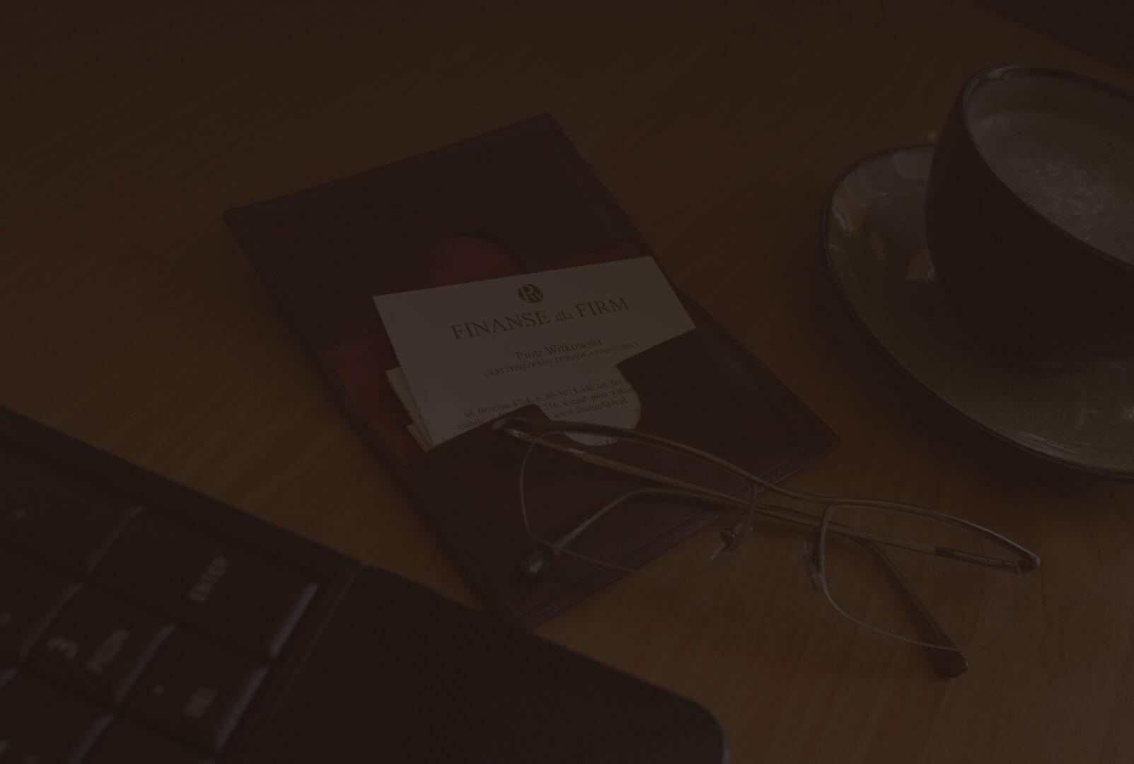 okulary leżące na otwartym wizytowniku z wizytówkami Finanse dla Firm